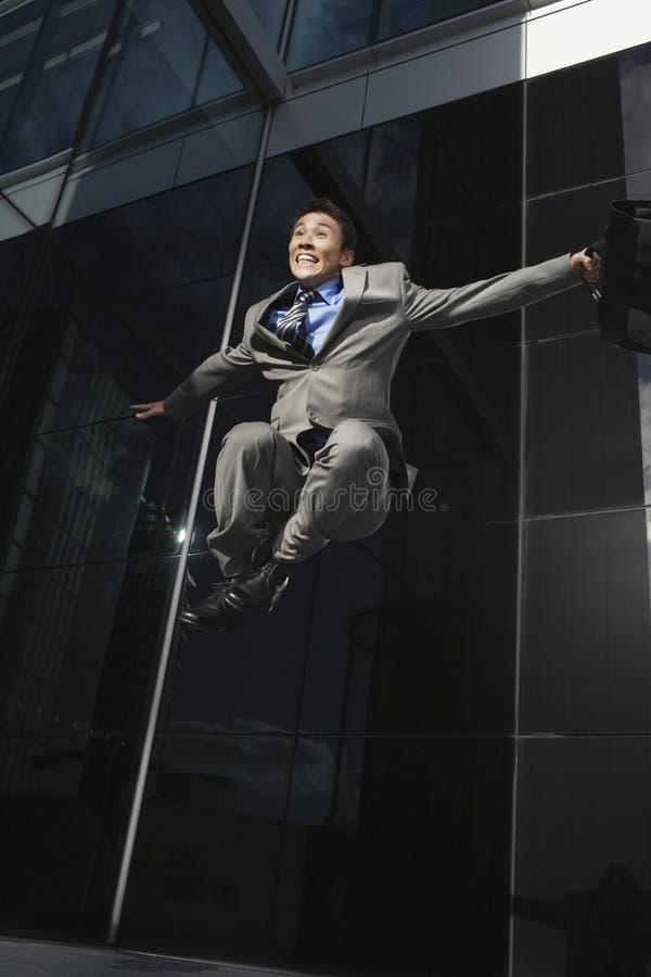Uomo d'affari With Briefcase Jumping fuori dell'ufficio fotografie stock
