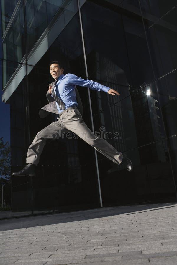 Uomo d'affari With Briefcase Jumping fuori dell'ufficio fotografia stock libera da diritti