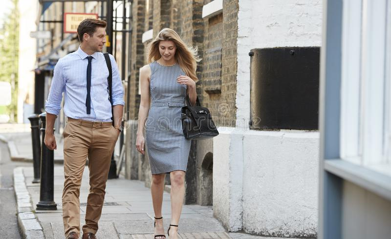 Uomo d'affari And Businesswoman Walk da lavorare tramite la via della città fotografia stock libera da diritti