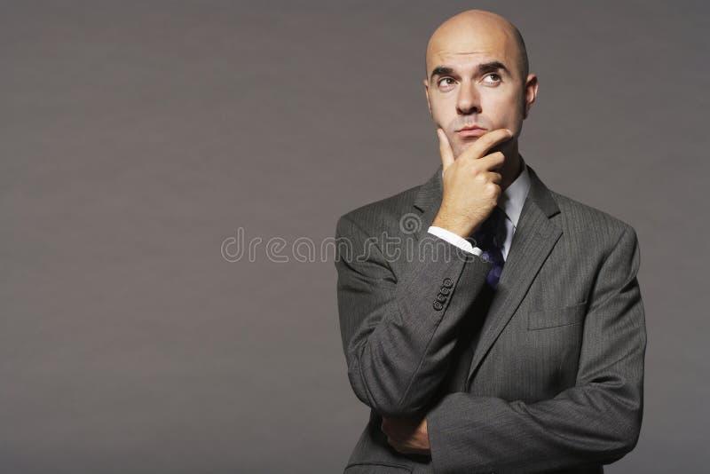 Uomo d'affari calvo With Hand On Chin Thinking fotografie stock libere da diritti