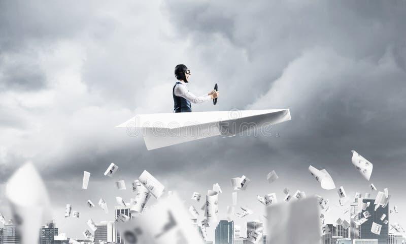 Uomo d'affari in cappello dell'aviatore che conduce l'aereo della carta immagine stock