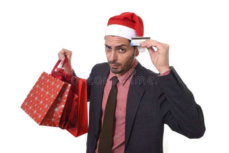 Uomo d'affari in cappello di Santa Claus Christmas che tiene le borse fradicie e la carta di credito in preoccupato in e sforzo immagine stock libera da diritti