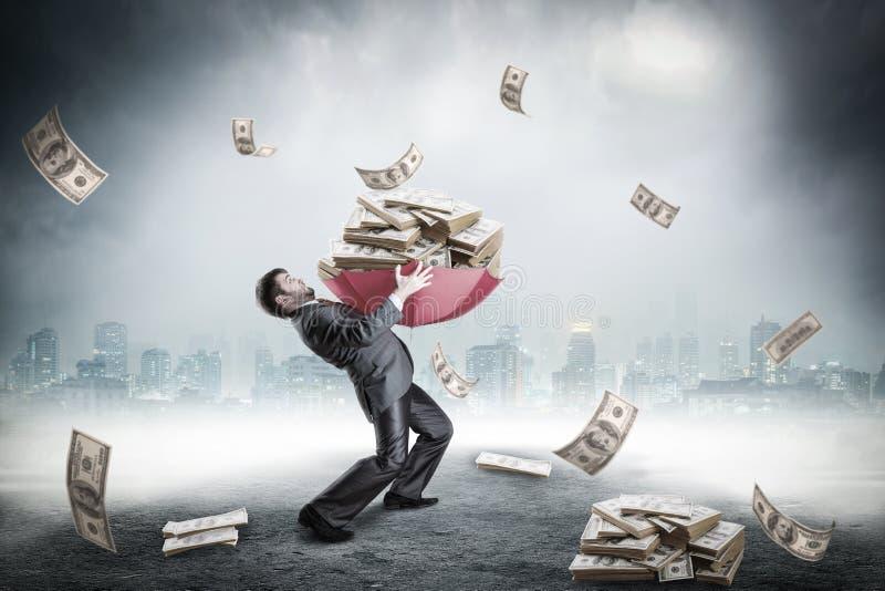 Uomo d'affari caricato con il gran quantità di soldi immagini stock