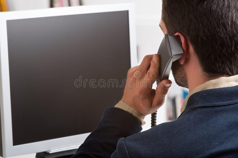 Uomo d'affari casuale che discute a fondo il telefono e che esamina un Compu immagine stock libera da diritti