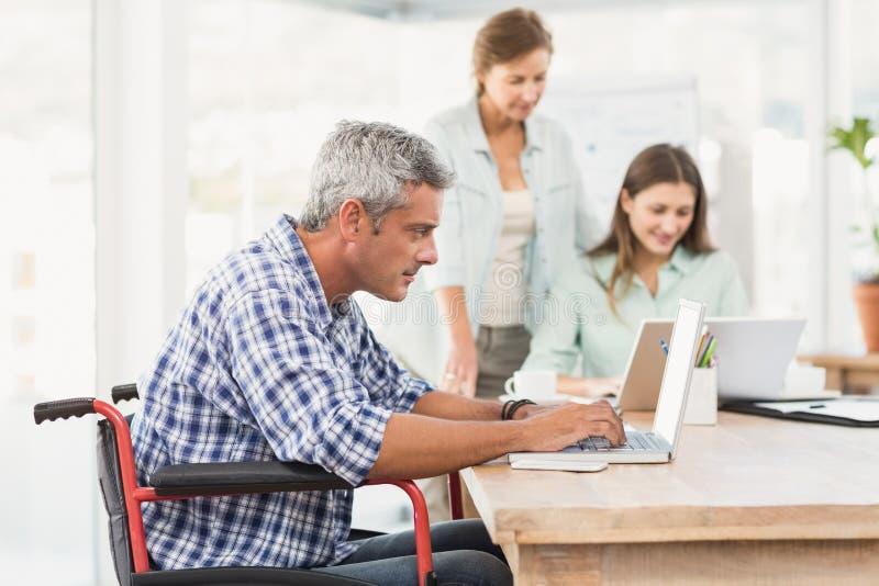 Uomo d'affari casuale in sedia a rotelle facendo uso del computer portatile fotografia stock