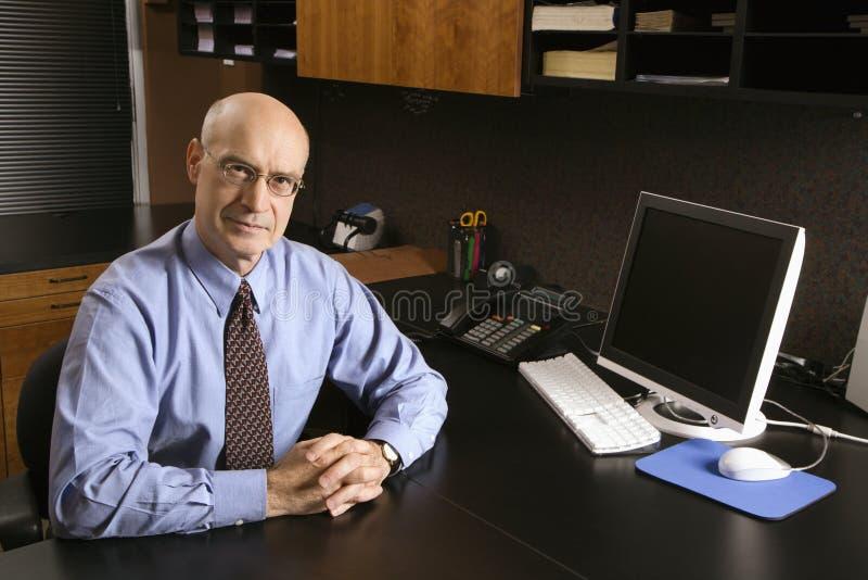 Uomo d'affari caucasico allo scrittorio. immagine stock