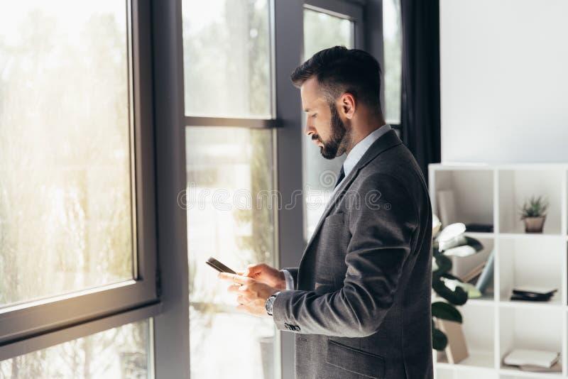 Uomo d'affari caucasico che scrive sullo smartphone all'ufficio moderno fotografia stock libera da diritti