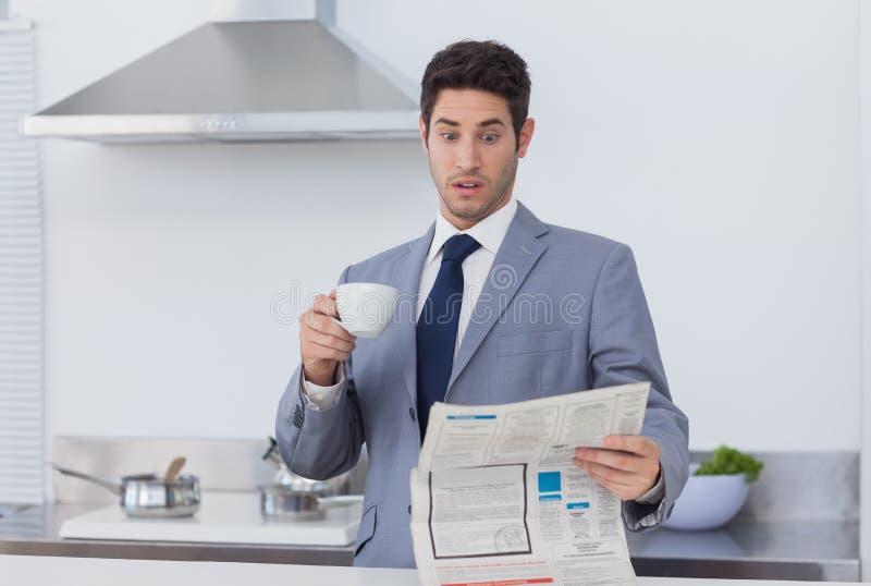 Uomo d'affari che è incredibile quando leggono le notizie fotografia stock