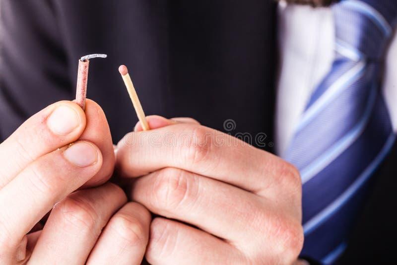Uomo d'affari che accende un petardo minuscolo immagini stock libere da diritti