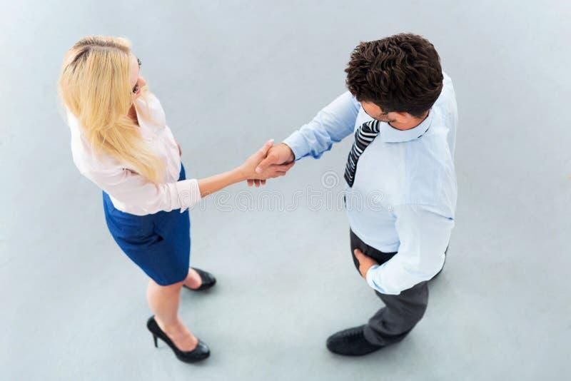Uomo d'affari che agita le mani con una donna di affari fotografia stock libera da diritti
