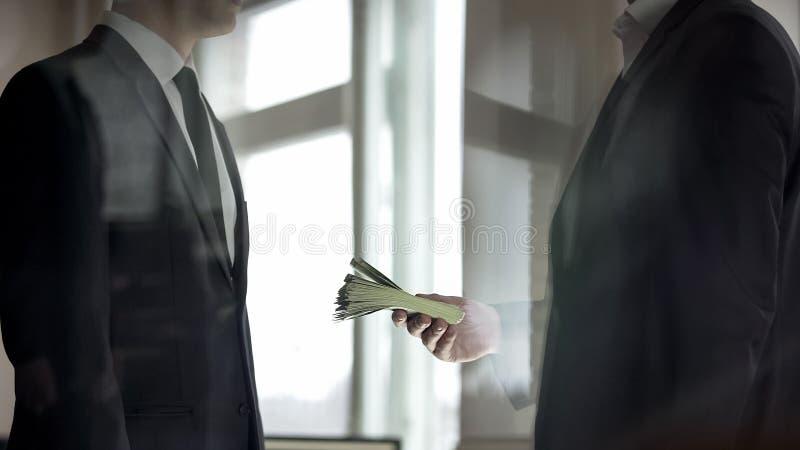 Uomo d'affari che d? al suo partner contanti, profitto dal riuscito affare di affari fotografie stock