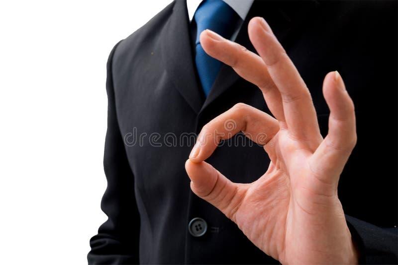 Uomo d'affari che alza la sua mano sinistra che dice OKAY fotografie stock libere da diritti