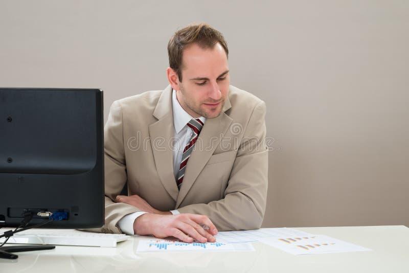 Download Uomo D'affari Che Analizza Grafico In Ufficio Fotografia Stock - Immagine di economico, azienda: 55351920