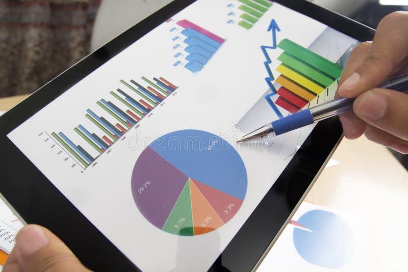Uomo d'affari che analizza le statistiche finanziarie visualizzate sullo schermo della compressa con una penna fotografie stock libere da diritti