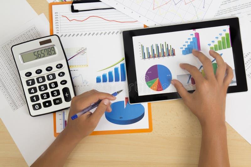 Uomo d'affari che analizza le statistiche finanziarie visualizzate sullo schermo della compressa con una penna fotografia stock libera da diritti