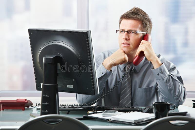 Uomo d'affari che ascolta la chiamata della linea terrestre in ufficio fotografia stock