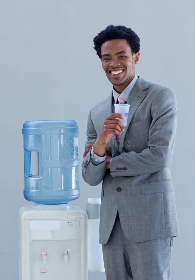 Uomo d'affari che beve da un dispositivo di raffreddamento di acqua in ufficio fotografia stock libera da diritti