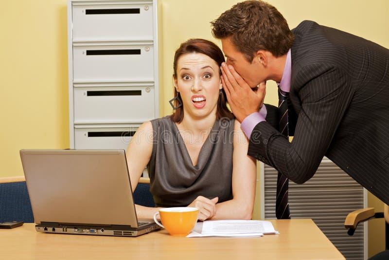 Uomo d'affari che bisbiglia in orecchio della donna di affari all'ufficio immagini stock libere da diritti