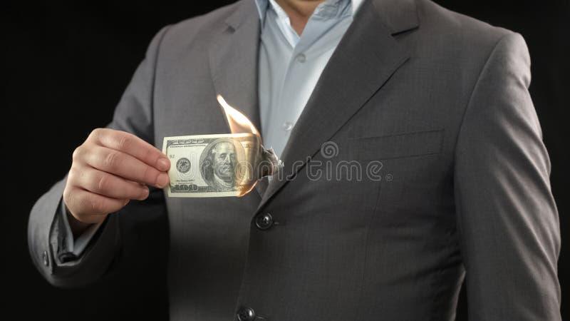 Uomo d'affari che brucia cento banconote in dollari, concetto di fallimento di crisi finanziaria fotografia stock libera da diritti