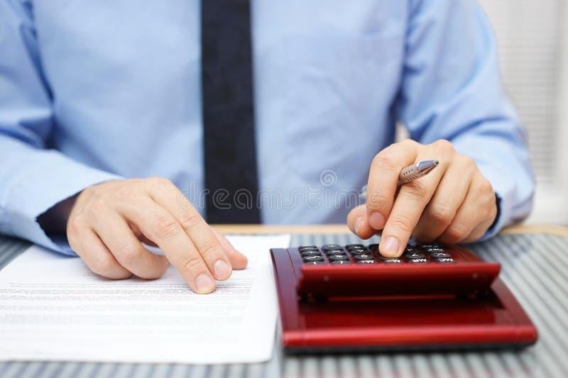 Uomo d'affari che calcola e che controlla gli articoli di accordo immagine stock