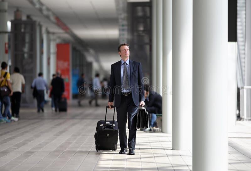 Uomo d'affari che cammina con il carrello attraverso la folla su un viaggio d'affari fotografie stock