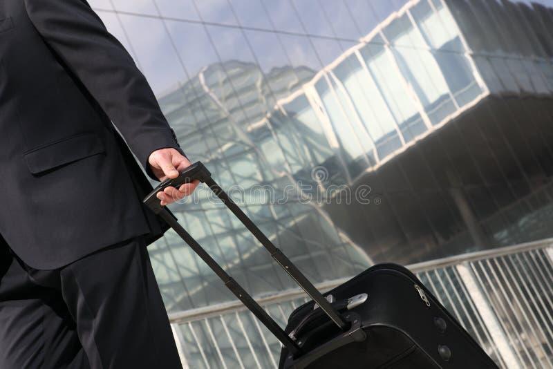 Uomo d'affari che cammina con il carrello, viaggio d'affari fotografia stock libera da diritti