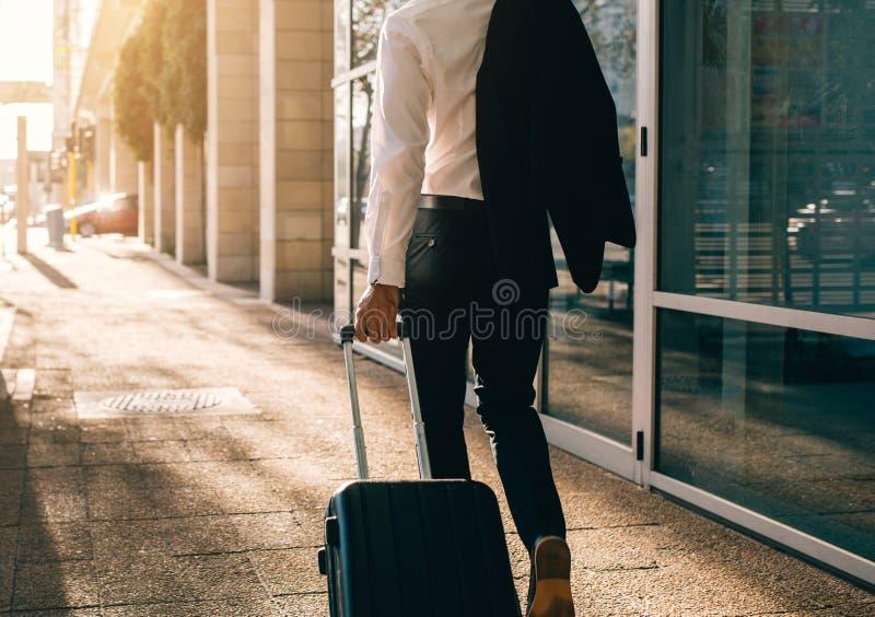 Uomo d'affari che cammina fuori dell'aeroporto con la valigia fotografia stock libera da diritti
