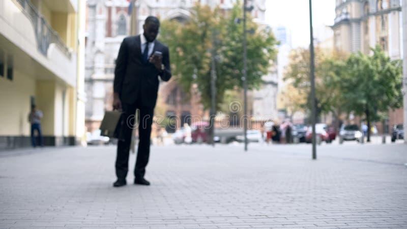 Uomo d'affari che cammina per lavorare e che per mezzo dello smartphone, stile di vita occupato in grande città fotografia stock libera da diritti