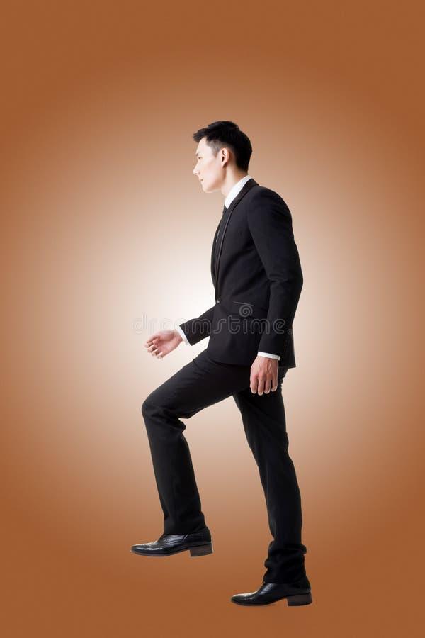 Uomo d'affari che cammina su sulle scale fotografia stock