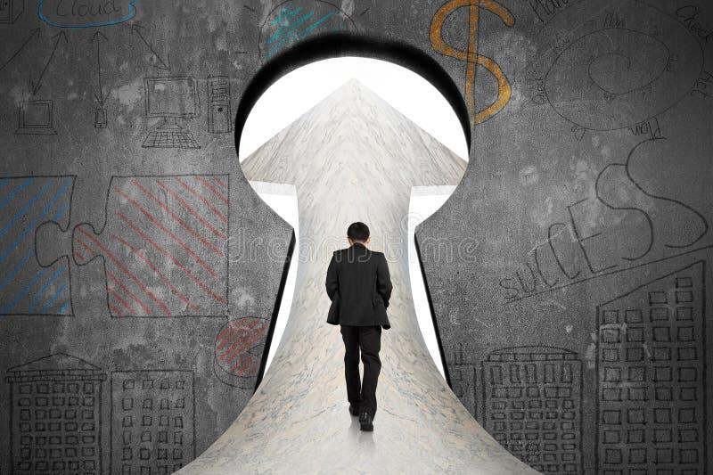 Uomo d'affari che cammina sulla strada di marmo verso la porta del buco della serratura con dood royalty illustrazione gratis