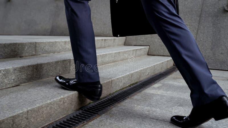 Uomo d'affari che cammina sulle scale, successo nel concetto di carriera, promozione, primo piano fotografie stock libere da diritti