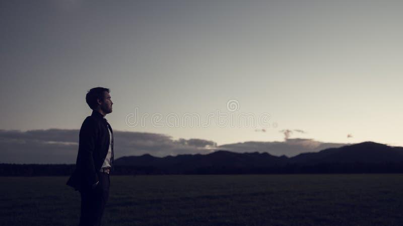 Uomo d'affari che celebra un nuovo giorno che sta in suo vestito fotografia stock libera da diritti