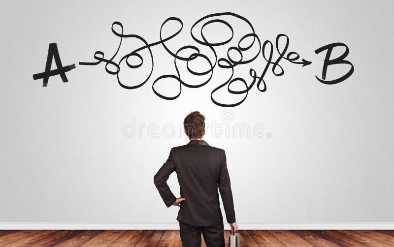 Uomo d'affari che cerca soluzione mentre stando davanti ad una parete fotografia stock