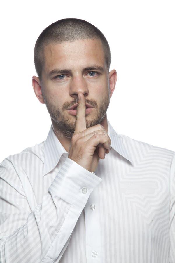 Uomo d'affari che chiede di tenere un secrect, isolato su fondo bianco immagine stock