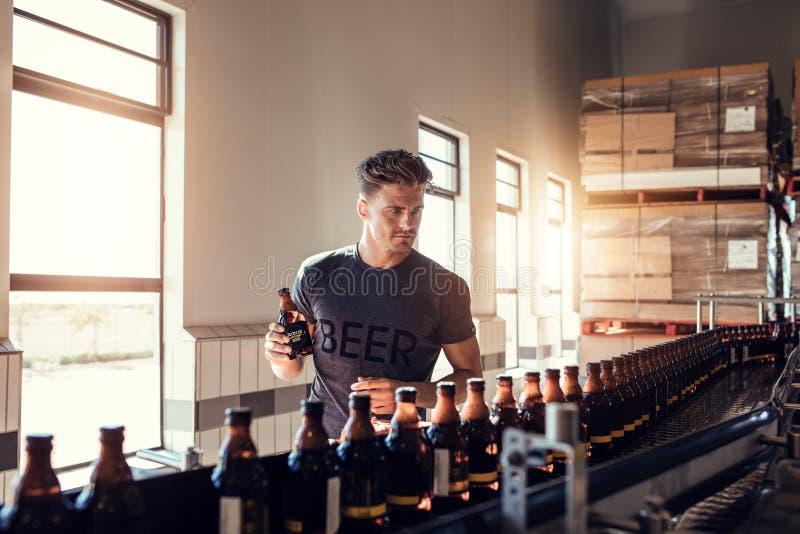 Uomo d'affari che collauda la bottiglia di birra alla fabbrica di birra fotografie stock libere da diritti