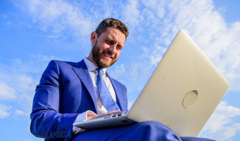 Uomo d'affari che comunica in linea Computer portatile di battitura a macchina sorridente del email del fronte piacevole dell'uom immagini stock