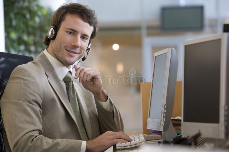 Uomo d'affari che comunica su una cuffia avricolare immagine stock