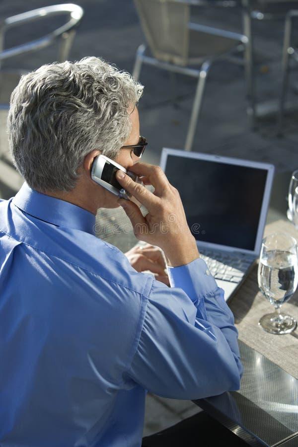 Uomo d'affari che comunica sul cellulare. immagine stock