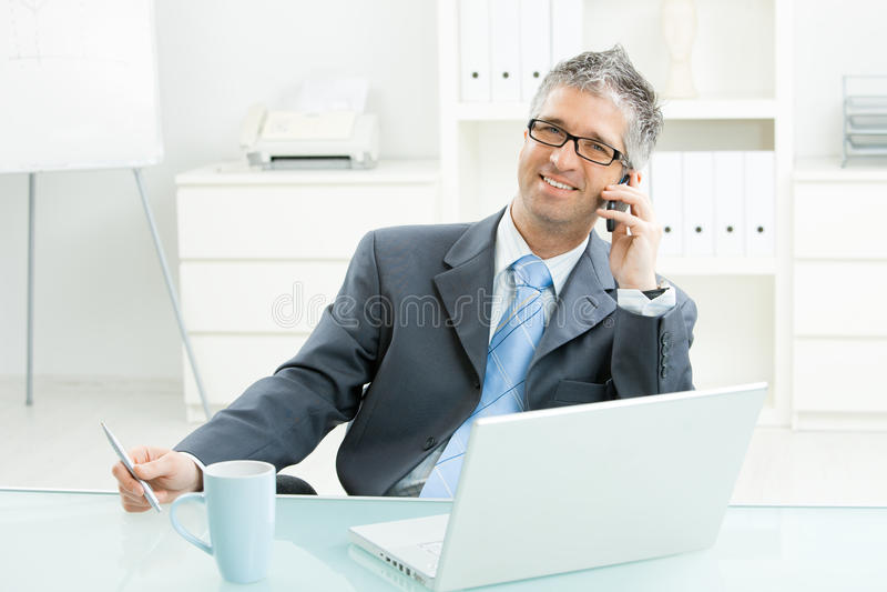 Uomo d'affari che comunica sul telefono mobile immagine stock libera da diritti