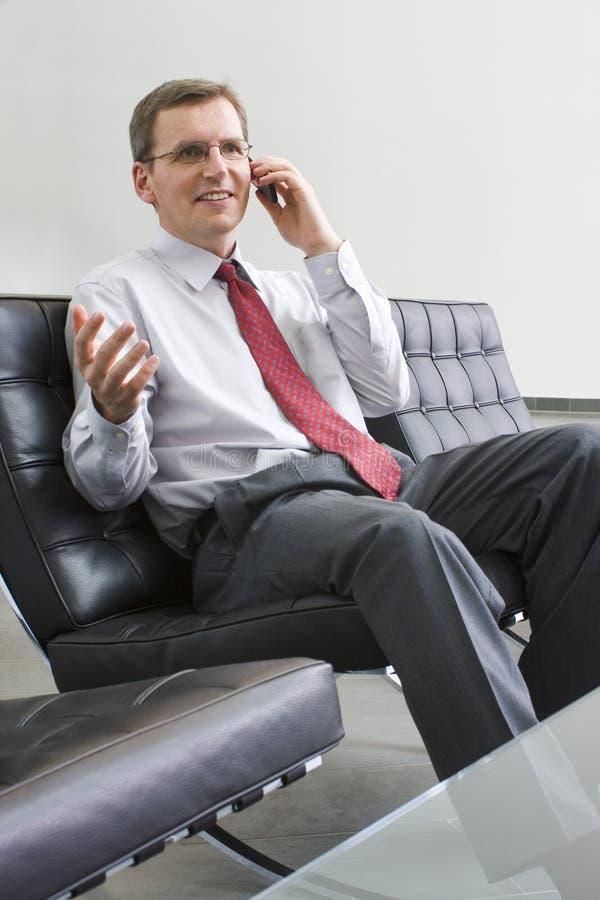 Uomo d'affari che comunica sul telefono mobile fotografie stock libere da diritti
