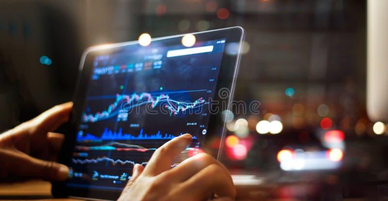 Uomo d'affari che controlla i dati del mercato azionario sulla compressa fotografie stock