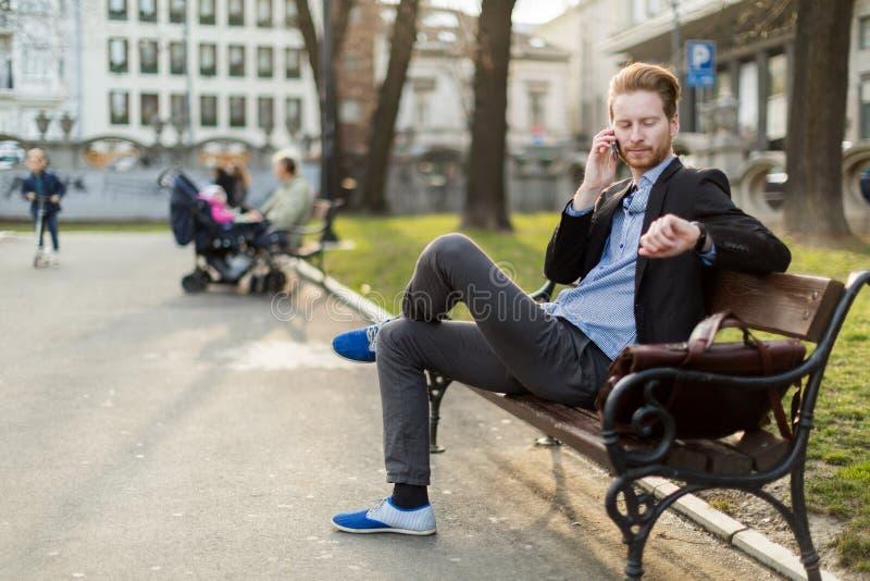 Uomo d'affari che controlla il tempo che esamina il suo orologio sul da soleggiato fotografia stock libera da diritti