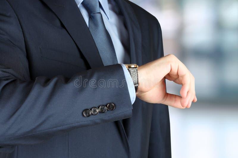 Uomo d'affari che controlla tempo sul suo orologio fotografie stock libere da diritti