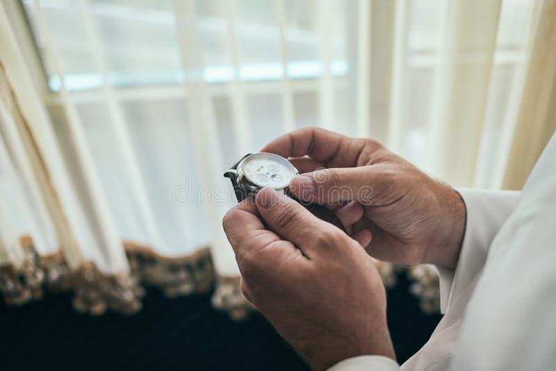 Uomo d'affari che controlla tempo sul suo orologio, uomo che mette orologio a disposizione, sposo che si prepara di mattina prima fotografie stock libere da diritti