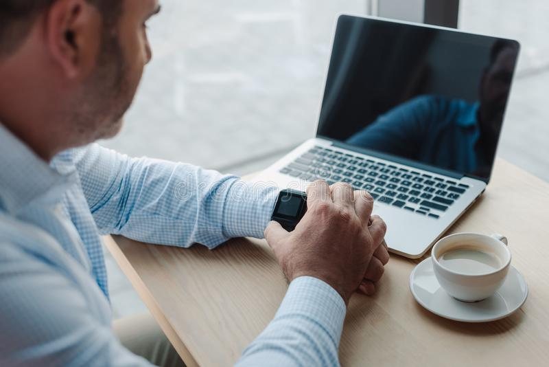 uomo d'affari che controlla tempo sull'orologio astuto mentre lavorando con il computer portatile fotografie stock