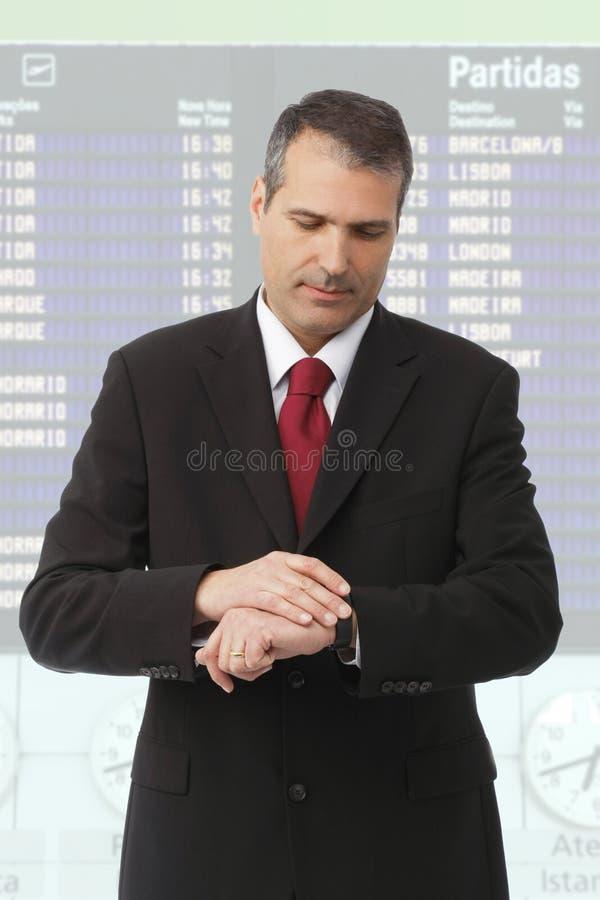 Uomo d'affari che controlla tempo sulla sua vigilanza immagini stock libere da diritti