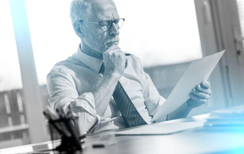 Uomo d'affari che controlla un documento; effetto della luce immagini stock