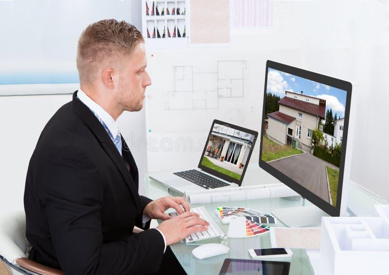 Uomo d'affari che controlla una cartella di proprietà online fotografia stock