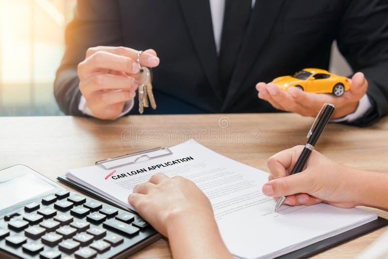 Uomo d'affari che dà chiave dell'automobile ed accordo di prestito di firma del cliente w immagine stock