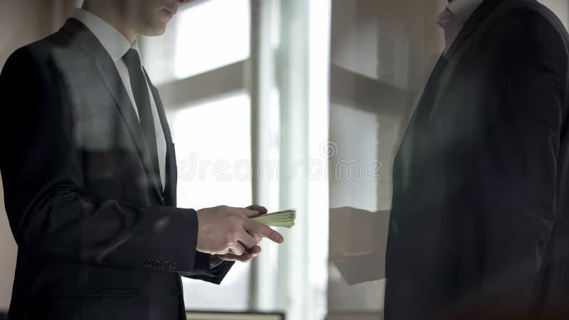 Uomo d'affari che d? soldi al partner, profitto dal riuscito affare di affari fotografie stock